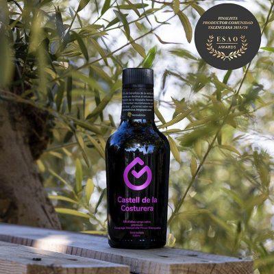 botella aceite entre ramas de olivo