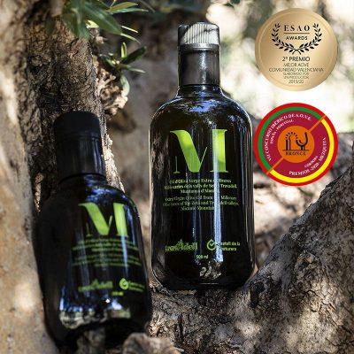 dos botellas de aceite entre ramas de olivo